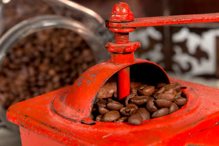 caffeinated: Roasted coffee beans being grinded in traditional style with an old manual coffee grinder