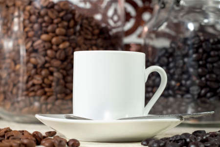 coffea: White coffee cup in front of glass pots with different types of roasted coffee beans Stock Photo