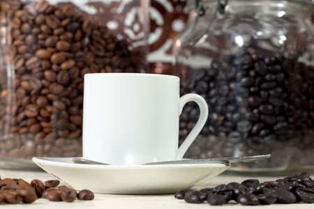 drupe: White coffee cup beside different types of roasted coffee beans
