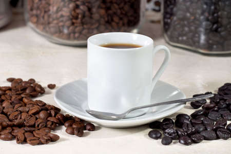 drupe: Cup of coffee beside natural roasted and torrefacto coffee beans