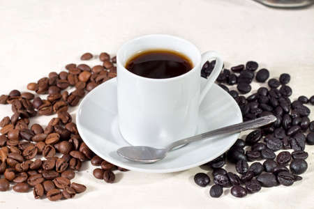 caffeinated: Cup of coffee beside natural roasted and torrefacto coffee beans, on white table