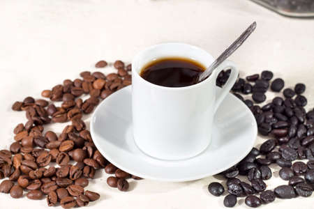 caffeinated: Coffee cup over a saucer, beside natural roasted and torrefacto coffee beans