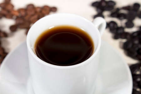 drupe: Close-up of coffee cup beside natural roasted and torrefacto coffee beans, on a white table Stock Photo