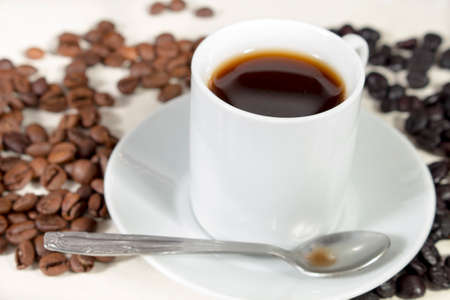 caffeinated: Coffee cup and teaspoon over a saucer, beside natural roasted and torrefacto coffee beans Stock Photo