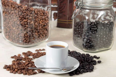 coffea: Coffee cup beside different types of roasted coffee beans