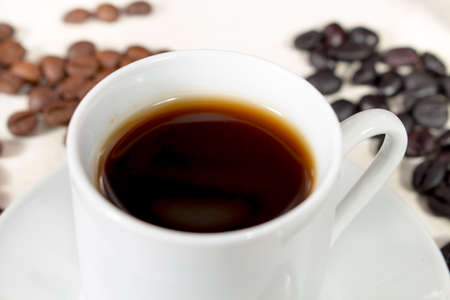 seed pots: Detail view of coffee cup beside natural roasted and torrefacto coffee beans, on a white table Stock Photo