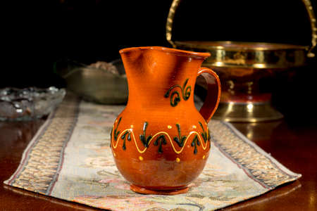 embroidered: Pottery jug to serve wine or water on an embroidered table mat Stock Photo