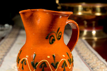 embroidered: Close-up of pottery jug to serve wine or water on an embroidered table mat Stock Photo