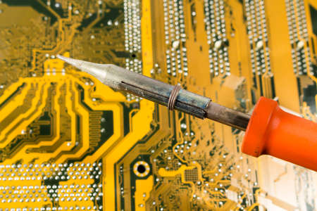 printed circuit: Soldering iron with red handle over a printed circuit board Stock Photo