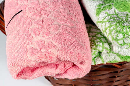 hand towel: Close-up of pink hand towel into a wicker basket