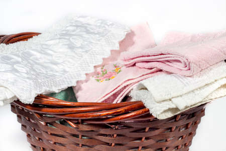 basket embroidery: Wicker basket full of hand towels of different colors and patterns Stock Photo