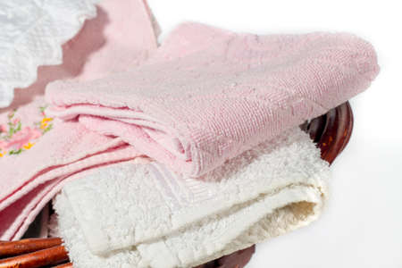 basket embroidery: Detail of different hand towels (pink and white) on a wicker basket Stock Photo