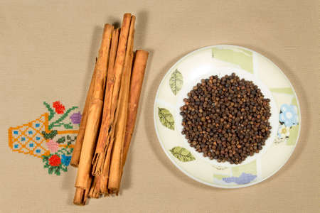 cinnamomum: Cinnamon sticks beside a dish with black pepper grains, on an embroidered cloth