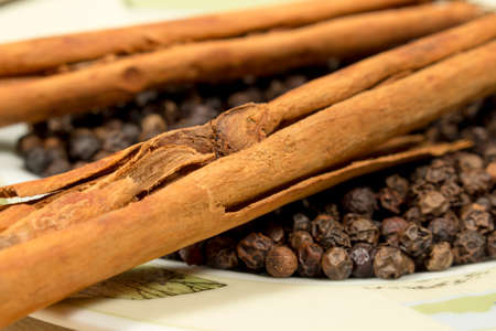 peppery: Close-up of cinnamon sticks and black pepper grains