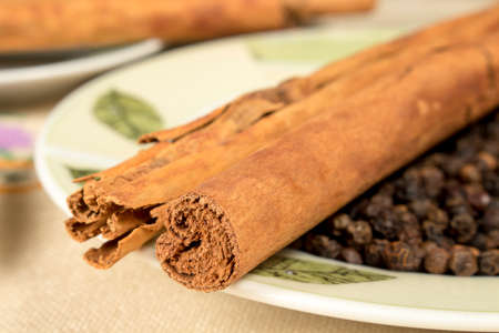 peppery: Close-up of cinnamon sticks and black pepper grains on decorated dish