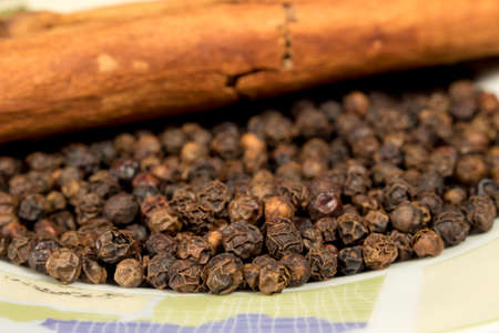 cinnamomum: Black pepper grains and cinnamon on decorated dish Stock Photo