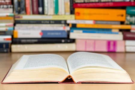 Livre ouvert sur un bureau en bois, avec des tas de livres à l'arrière-plan