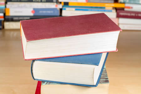pedagogic: Pile of books on a wooden desk, with other books at background Stock Photo