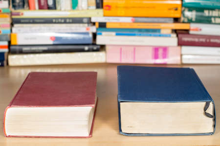 Red and blue books on a clear wooden desk