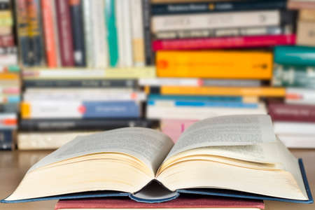 pedagogic: Open book in front of other books Stock Photo