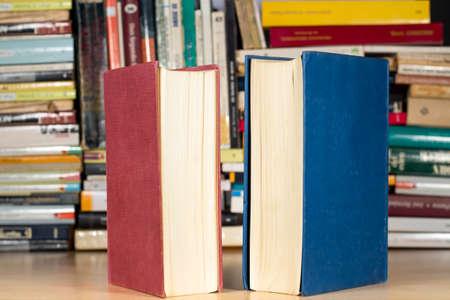 Deux livres avec des couvertures bleues et rouges devant d'autres livres