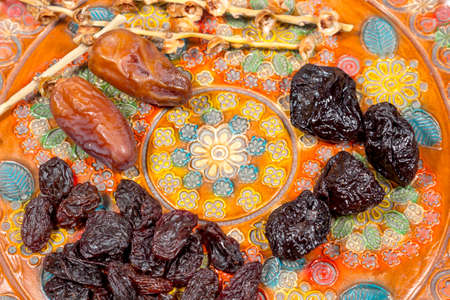 phoenix dactylifera: Dates, prunes and raisins on a pottery tray with floral decoration