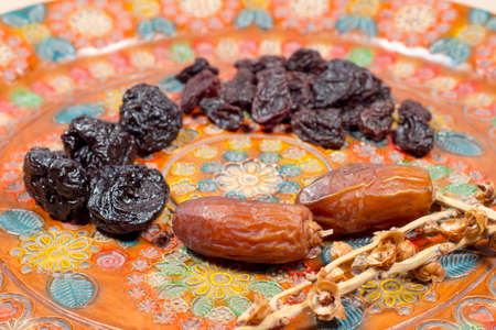dactylifera: Two dates beside prunes and raisins on a pottery tray with floral decoration Stock Photo