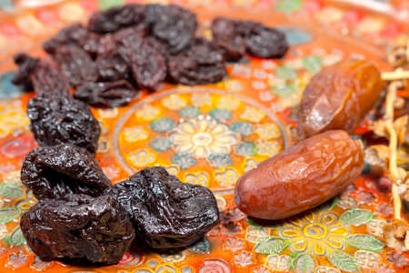 phoenix dactylifera: Several prunes beside dates and raisins on a pottery tray with floral decoration