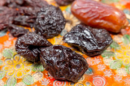 phoenix dactylifera: Close-up view of prunes beside dates and raisins on a pottery tray with floral decoration Stock Photo