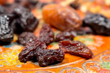 phoenix dactylifera: Several raisins in front of dates and prunes, on a pottery tray with floral decoration