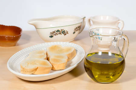 cruet: Crystal cruet containing Extra Virgin olive oil beside a dish with several toasts. Mediterranean breakfast Stock Photo