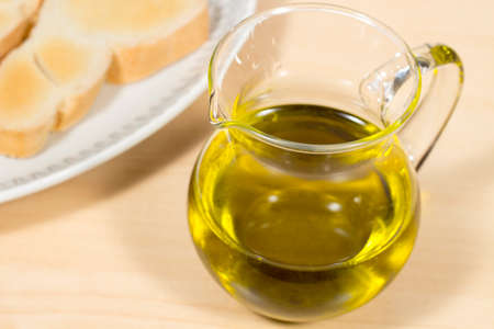 cruet: Extra Virgin olive oil into a crystal cruet, beside a dish with toasted slces of bread. Mediterranean breakfast