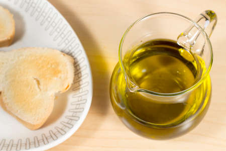 cruet: Crystal cruet with Extra Virgin olive oil beside a dish with toasted slces of bread. Mediterranean breakfast