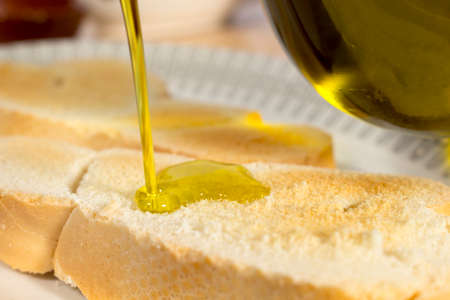 extra virgin: Pouring Extra Virgin olive oil on a slice of toasted bread. Mediterranean breakfast