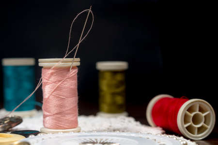 crocheted: Threaded needle in a spool of pink thread, on a white crocheted doily and black background Stock Photo