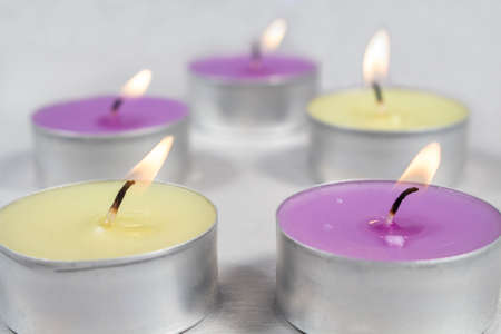 vax: Scented candles with metal base, light green (apple fragrance) and purple (lilac fragrance), on clear fllor
