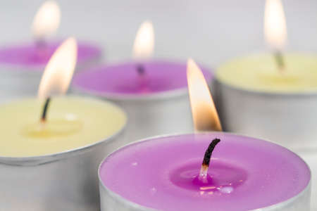 vax: Lilac scentled candle in front of other ones with te same fragrance and green apple Stock Photo