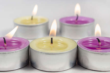 vax: Scented candle with green apple fragrance beside others with lilac fragrance Stock Photo