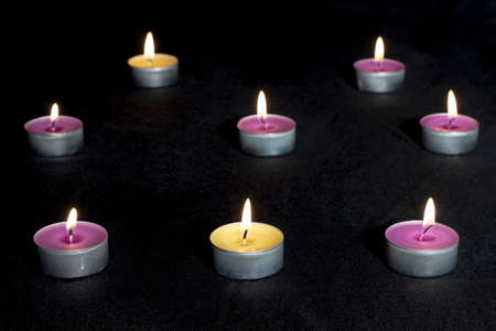 vax: Scented candles of different fragrances, with metal base, on black