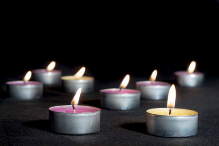 vax: Scented candles of different fragrances, with metal base, on black background Stock Photo