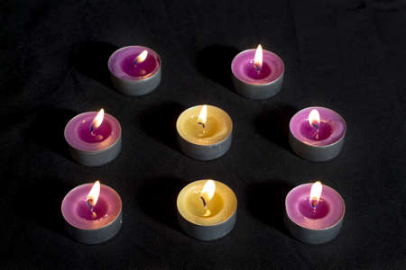 vax: Scented candles with metal base, smelling lilacs and green apples (at center), on dark floor