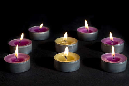 vax: Small scented candles with metal base, smelling lilacs and green apples (at center), on dark floor Stock Photo