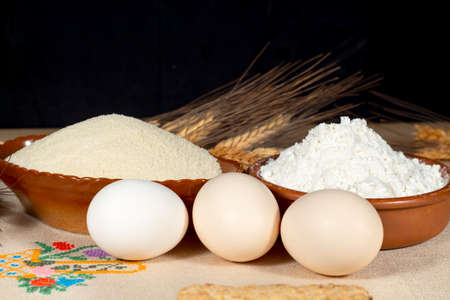 Several chicken eggs beside wheat flour, breadcrumbs and wheat spikes. Staple foods. Stock Photo