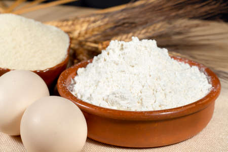 breadcrumbs: Chicken eggs beside wheat flour, breadcrumbs and wheat spikes. Staple foods. Stock Photo