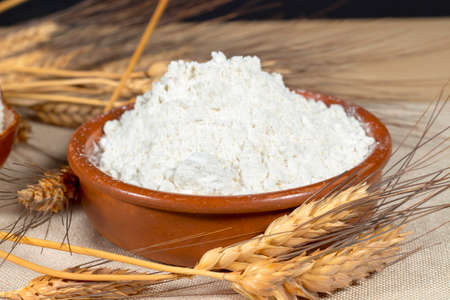 wheat flour: Wheat spikes beside a pottery bowl with pastry flour. Staple foods.