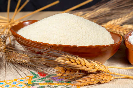 staple: Wheat spikes beside a pottery bowl with breadcrumbs, on an embroidered cloth. Staple foods.