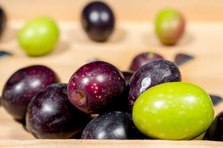 seasoned: Green olives beside other ones with different shades of color and ripening. Preparing seasoned table olives