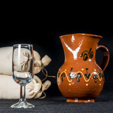 whine: Sherry glass beside a pottery jug to serve wine