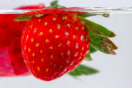sepals: Detail of strawberry submerged into a water glass