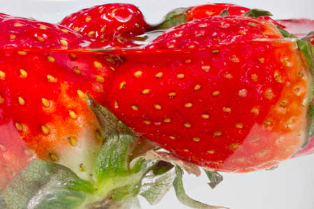 submerge: Detail view of strawberries dipped into water